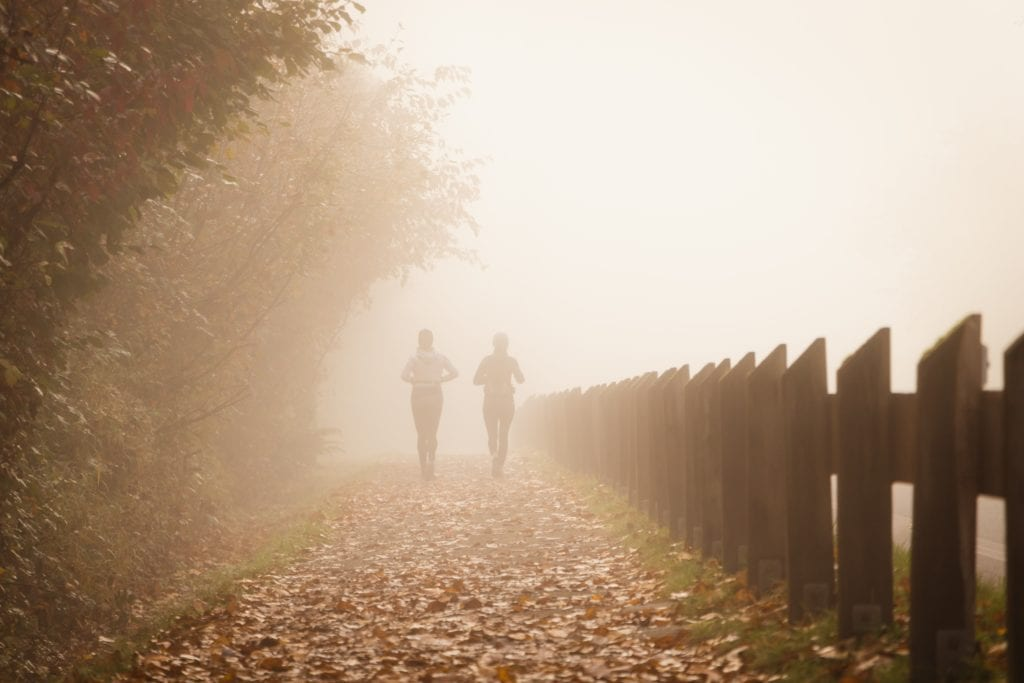 two female friends jogging on a foggy autumn trail away from the camera